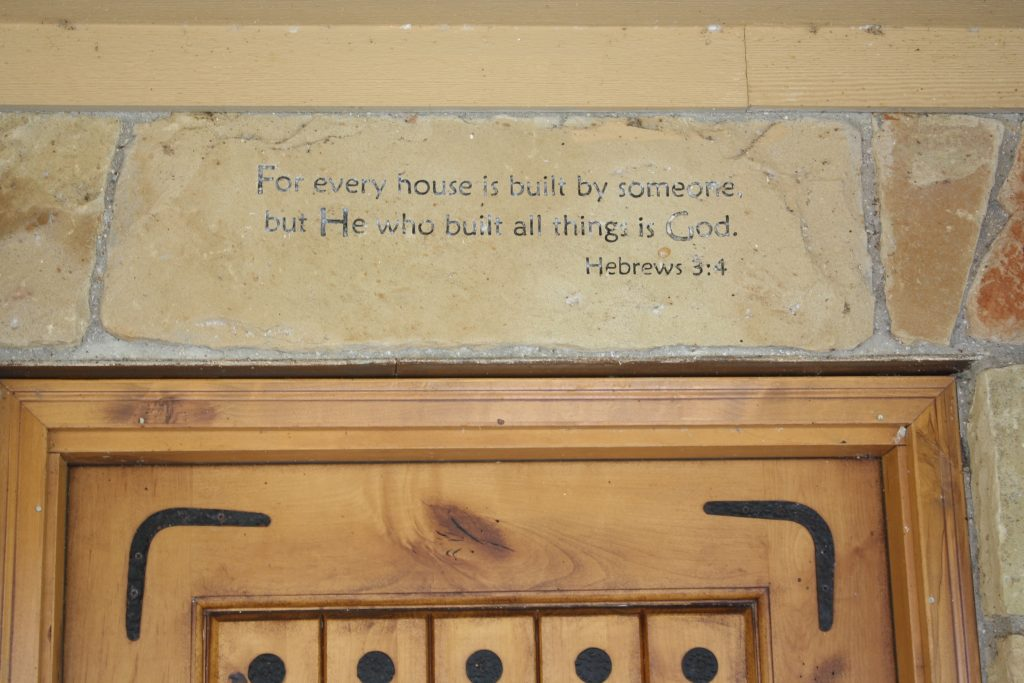 Bible verse carved above the entry of a home in the country.