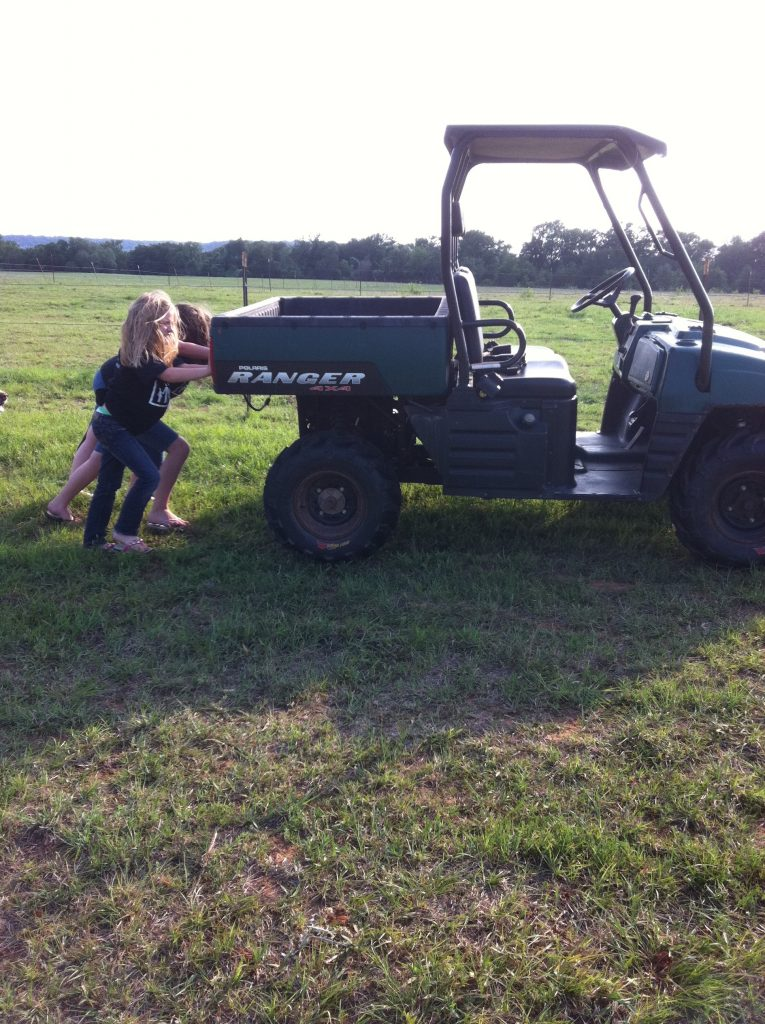 Two little girls pushing an off-road vehicle in a pasture.